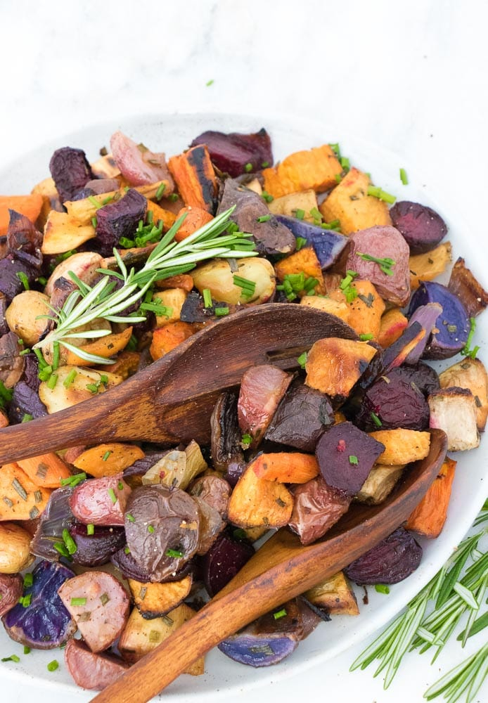 roasted vegetables garnished with herbs with wooden spoons