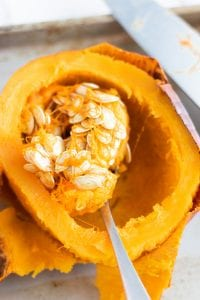 Scooping out seeds from oven baked halved pumpkin