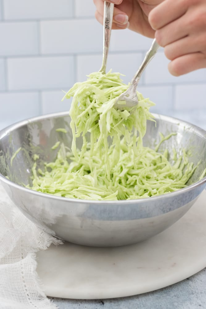 tossing coleslaw in bowl