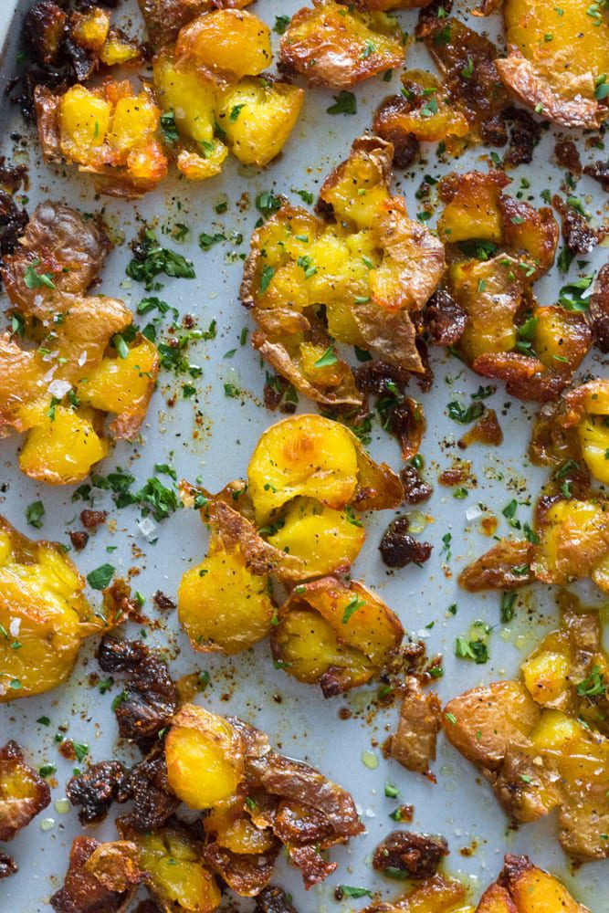 Crispy Smashed Potatoes shown on a white plate, sprinkled with parsley