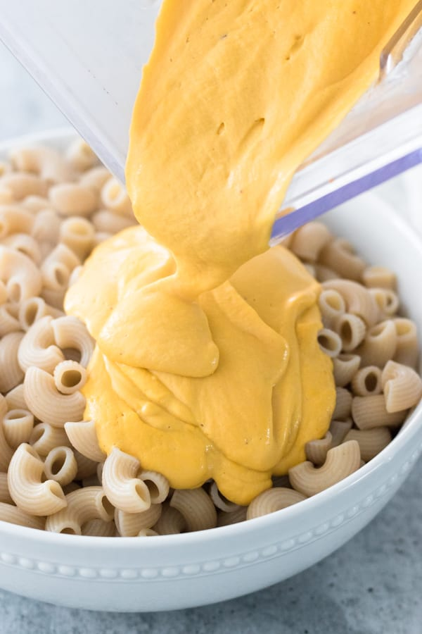 Pouring Vegan Mac N Cheese Sauce Over Elbow Noodles