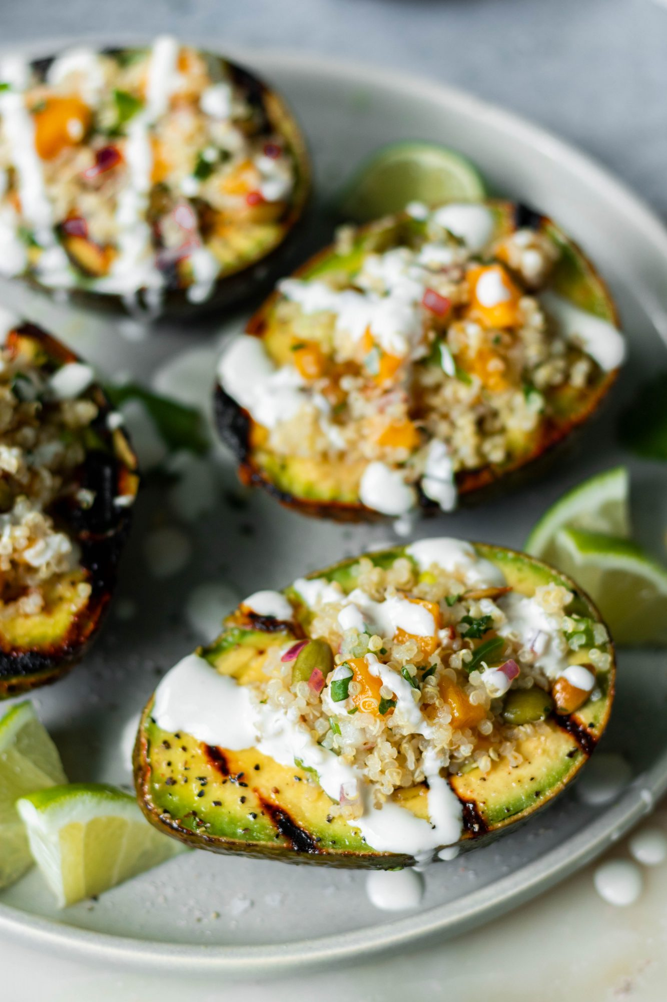 Grilled Avocados with Quinoa Mango Cilantro Salad Drizzled with Sour Cream
