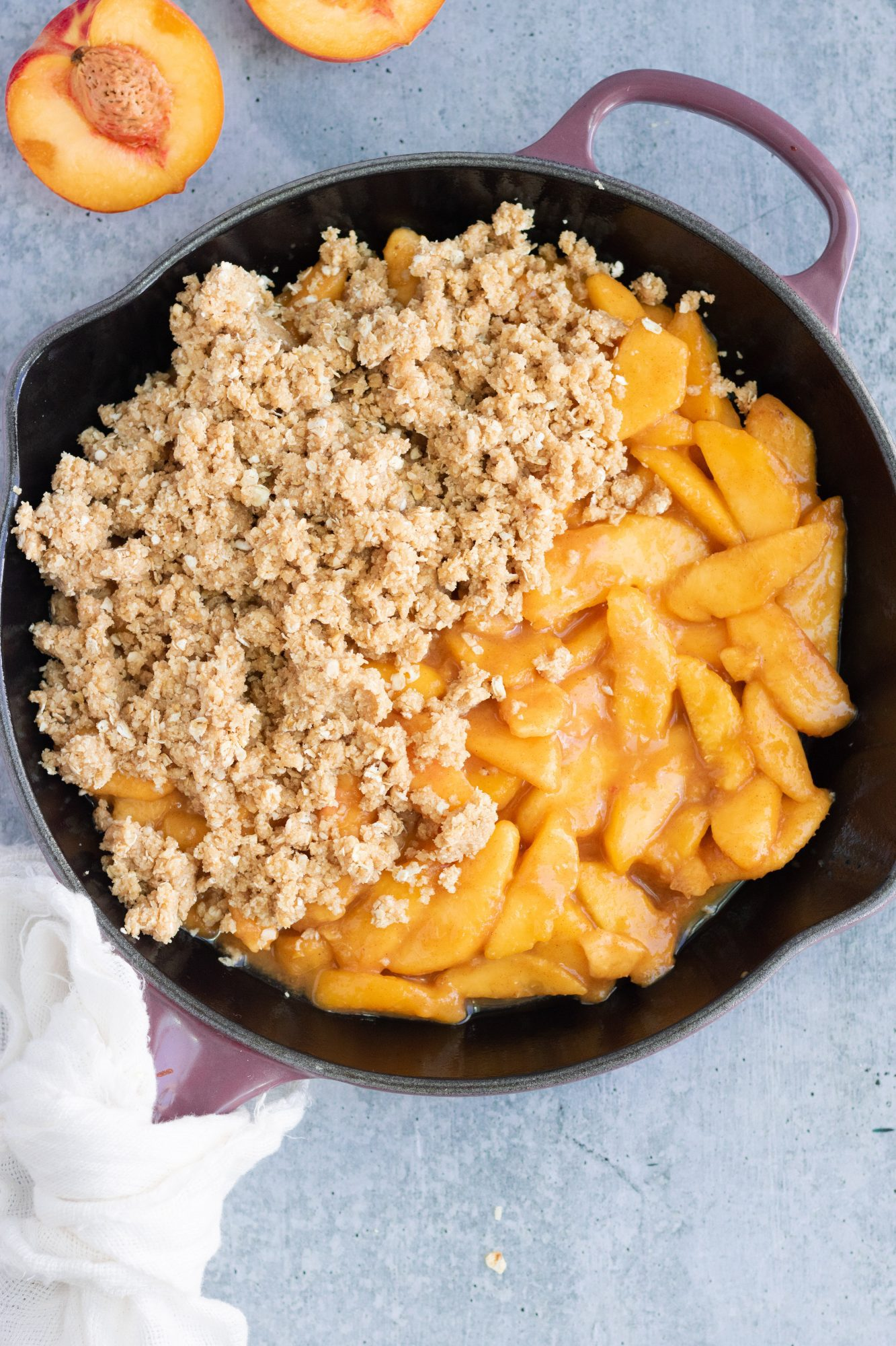 Peaches and cobbler topping in skillet before cooked