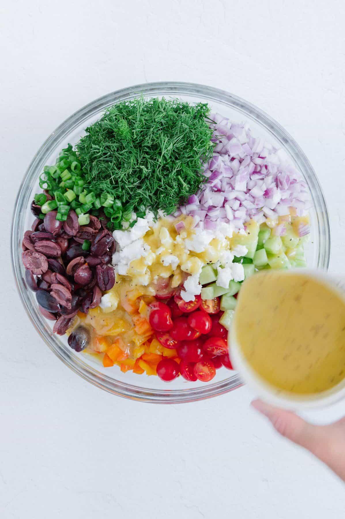 Pouring Dressing over Greek Pasta Salad